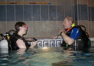 Instructor and student learning to dive in the pool